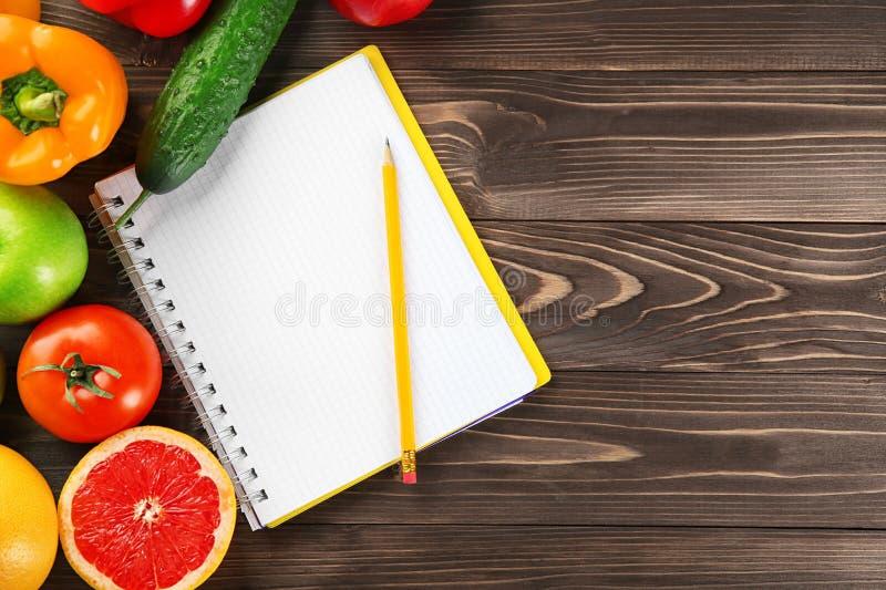 Gemüse, Früchte und Notizbuch auf hölzernem Hintergrund N?hren Sie Nahrung stockbild