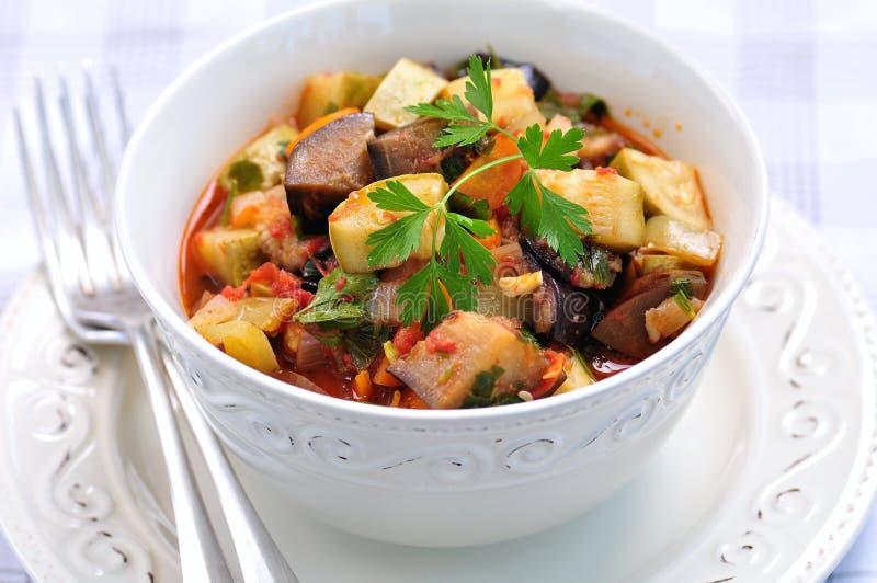 Gemüseeintopfgericht der Aubergine, der Zucchini, der Zwiebeln, der Karotten, der Tomaten, des Knoblauchs und der Petersilie stockfoto