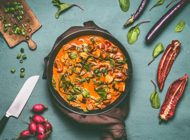 Gemüsehühnerwanne mit Currysoße auf Küchentischhintergrund mit Bestandteilen, Draufsicht, flache Lage stockbilder