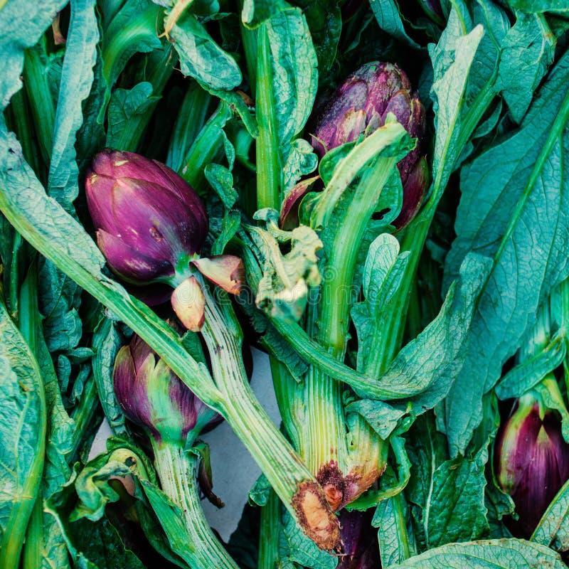 Gemüsehintergrund mit frischen Artischocken mit grünen Stämmen sta lizenzfreies stockfoto