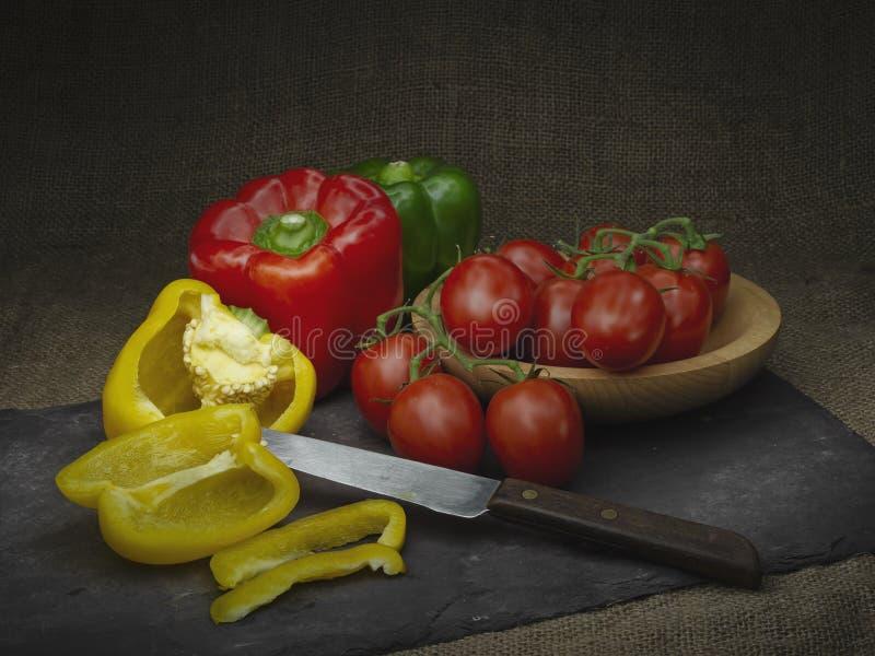Gemüsepaprikas und rote Tomaten, Stillleben Heller Anstrich Mit Retro- rustikalem Hintergrund des Messers und des Schiefers stockfoto