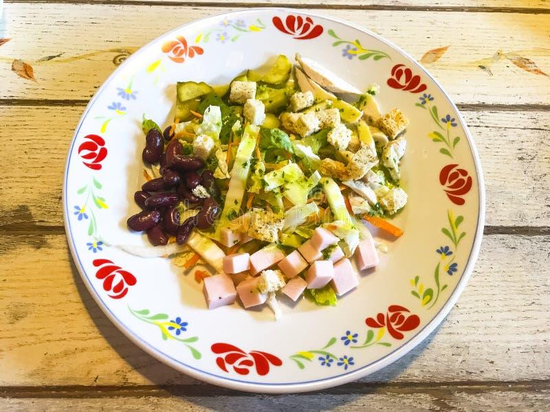 Gemüsesalat mit Wurst und Bohnen in der Platte auf altem Holztisch lizenzfreies stockbild