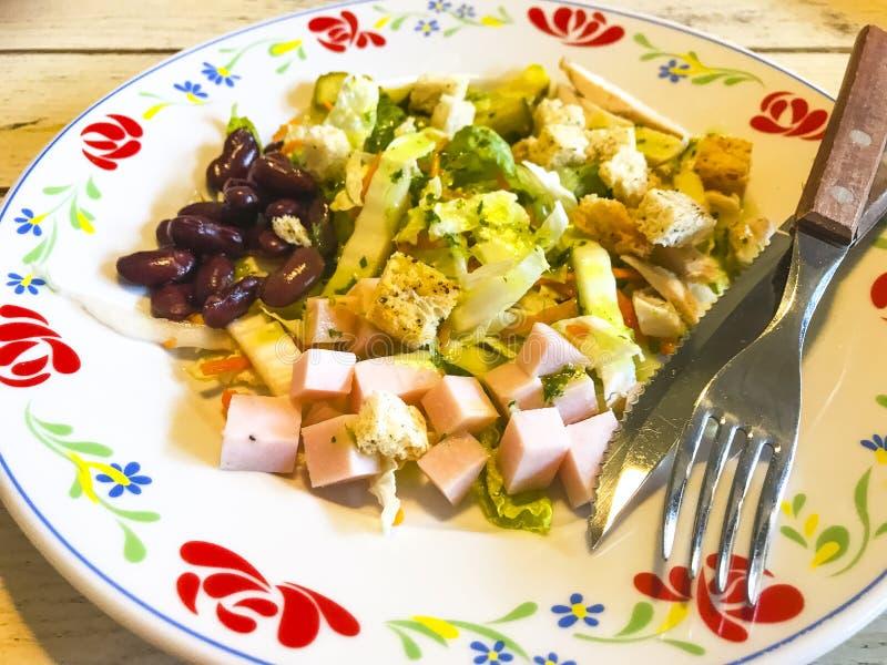 Gemüsesalat mit Wurst und Bohnen in der Platte auf altem Holztisch stockbild