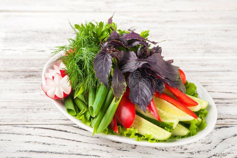 Gemüseservierplatte in einer weißen Plattennahaufnahme Gurken, Tomaten, Rettiche, Basilikum, Dill in einem Plattenkopienraum stockfoto