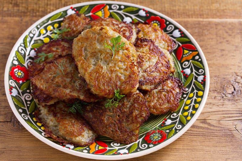Gemüsestückchen, Latkes, draniki, Bratkartoffeln - populärer Teller in vielen Ländern Vegetarischer gesunder Teller lizenzfreie stockbilder