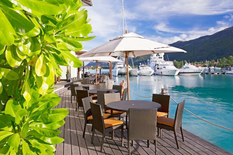 Gemütliche Gaststätte auf Decking durch den Jachthafen lizenzfreies stockfoto