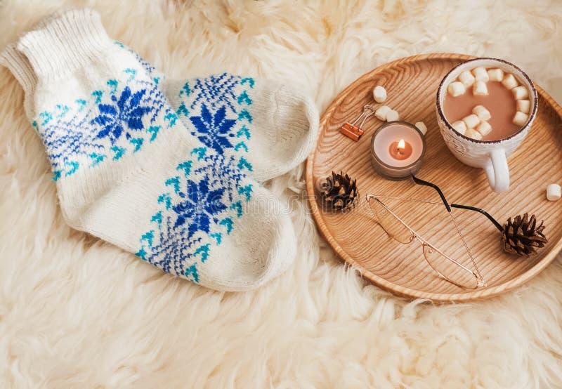 Gemütliche Herbst- oder Winterzusammensetzung mit gestrickten Socken, Kerzen und Kakao mit Eibischen stockfotos