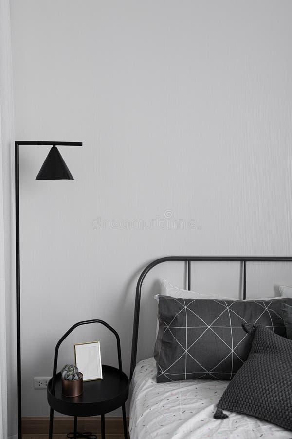 Gemütliche Schlafzimmerecke in der skandinavischen Art mit schwarzes Metallminimaler Stehlampe/Innenarchitekturdekoration stockfotos