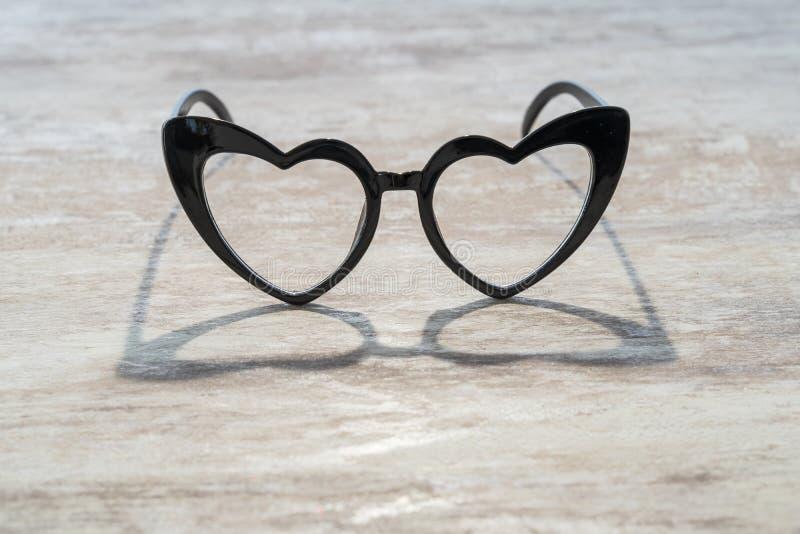 Gemütlicher hölzerner Hintergrund, mit Herz-förmigen Gläsern, der im Holz, Liebeskonzept, für Valentinstag reflektiert wird, das  lizenzfreie stockfotografie
