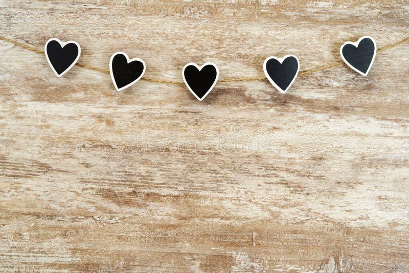 Gemütlicher hölzerner Hintergrund, wenn 5 schwarze Herzen zwischen ihnen befestigt sind, mit einem Hanfseil, Liebeskonzept, für V lizenzfreie stockfotografie