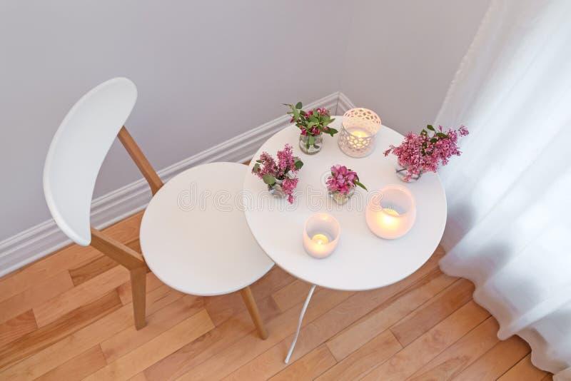 Gemütlicher Innenraum mit Kerzenlichtern und -frühling blüht stockfoto