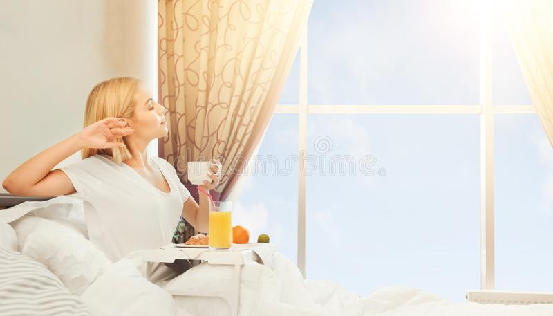 Gemütlicher Morgen im Hotelzimmer Frau, die im Bett fr?hst?ckt stockfotografie