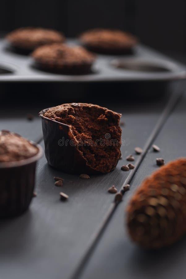 Gemütlicher Nachtisch Hygge Halb aufgegessene geschmackvolle Schokoladenmuffins mit kleinen Schokoladensplittern auf dunklem Hint stockfotos