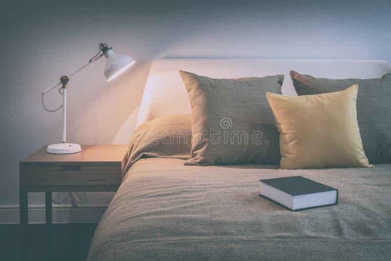 Gemütlicher Schlafzimmerinnenraum mit Buch und Leselampe auf Nachttisch stockfotografie