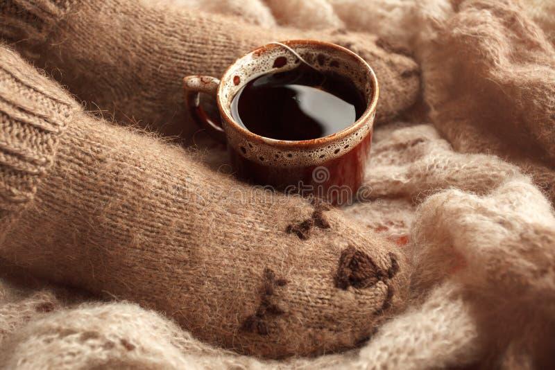 Gemütlicher Winterfall-Herbstlebensstil: Frauenfußbeine in den warmen netten Bärnsocken und Tasse Tee Retro- Tonen, beige Monochr lizenzfreie stockfotografie