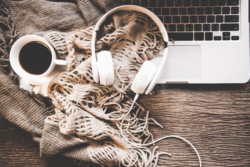 Gemütlicher Winterhintergrund, Schale heißer Kaffee mit Eibisch und Kopfhörermusik, wärmt gestrickte Strickjacke, Arbeitsplatzlap lizenzfreie stockfotos