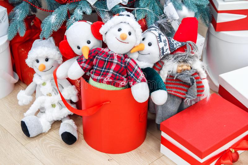 Gemütlicher Winterurlaubhintergrund Lustige Spielzeugschneemänner und -geschenke, die auf Weihnachten unter verziertem Tannenbaum lizenzfreies stockbild