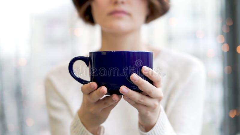 Gemütliches Atmosphärenmädchen mit großem Schalenkaffeekakaoschokoladenweihnachtszeitwinter Abschluss herauf die Hände der jungen lizenzfreie stockfotos