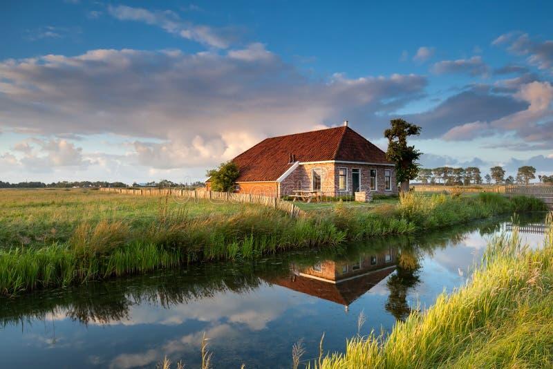 Gemütliches Bauernhaus im Goldsonnenuntergangsonnenlicht stockfotografie