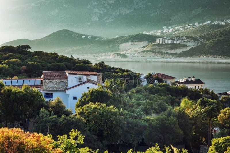 Gemütliches Dorf in den Bergen durch das Meer auf einem Sonnenunterganghintergrund Sonneneruption Sch?ne Landschaft stockbild