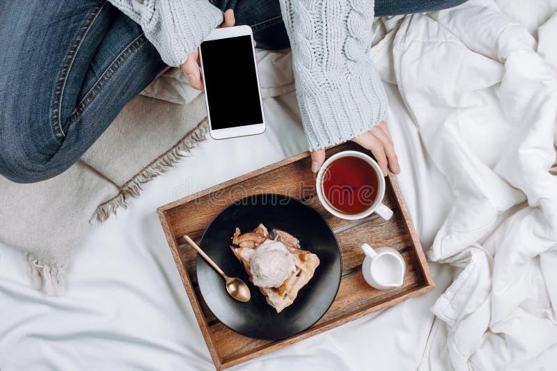 Gemütliches flatlay des Betts mit hölzernem Behälter mit Apfelkuchen des strengen Vegetariers, Eiscreme und schwarzem Tee lizenzfreie stockfotos