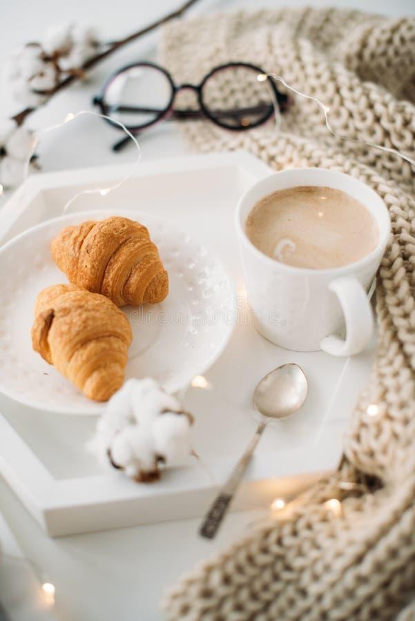 Gemütliches Hauptfrühstück, warme Decke, Kaffee und Hörnchen auf Weiß lizenzfreie stockbilder