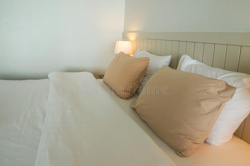 Gemütliches Kissen auf weißem Doppelbett im minimalen Hauptschlafzimmer lizenzfreies stockfoto