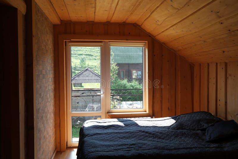 Gemütliches Schlafzimmer mit Fenster und hölzernen Wänden stockfotografie