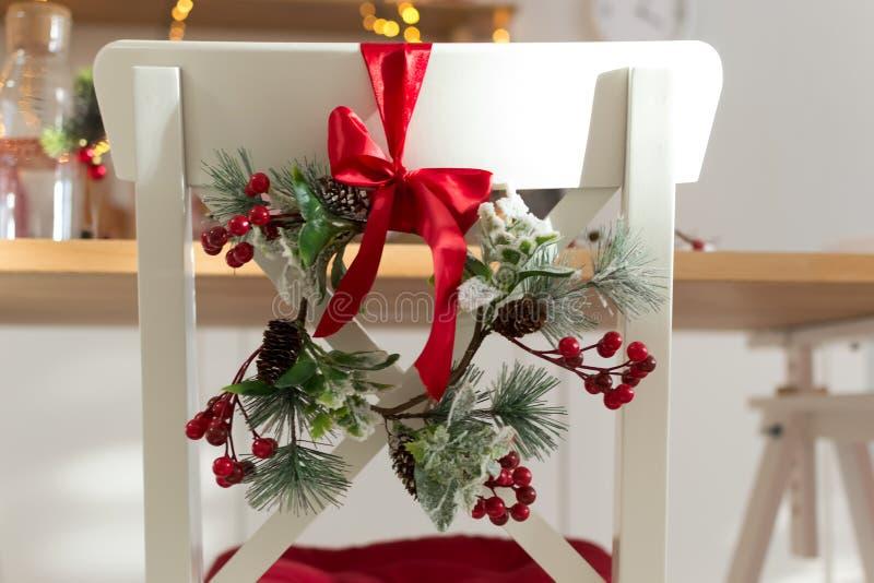 Gemütliches verziert mit Weihnachtsdekorationen mit rotem Band und weißem Küchenstuhl der Tannenzweige lizenzfreies stockbild
