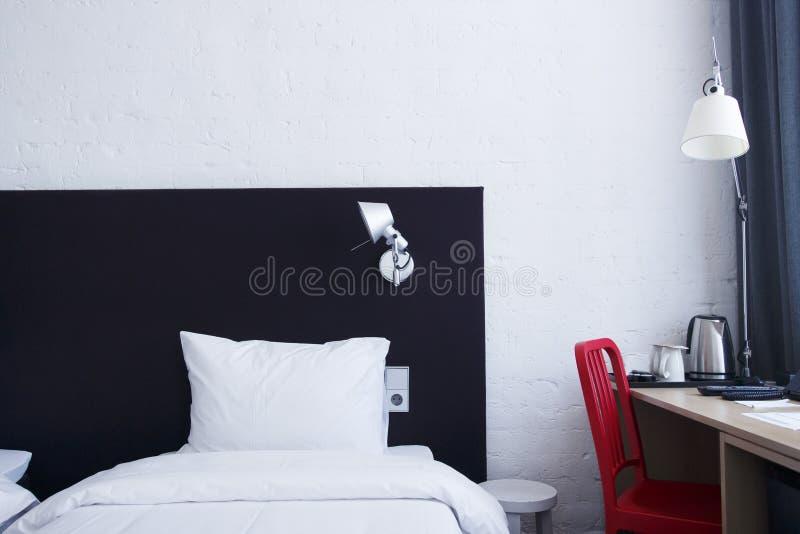 Gemütliches weißes Schlafenbett im Schlafzimmer mit Nachtlampe auf dem Tisch Helles Schlafzimmer in der Stadtwohnung stockfoto