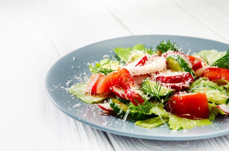 Gem?sesalat des neuen Fr?hlinges mit Rettich und Parmesank?se Platte mit Salat auf einem wei?en Holztisch stockbilder