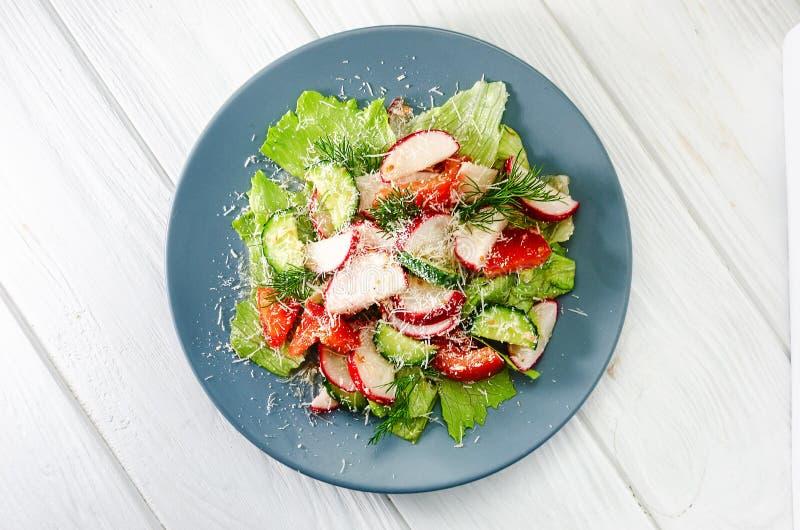 Gem?sesalat des neuen Fr?hlinges mit Rettich und Parmesank?se Platte mit Salat auf einem wei?en Holztisch lizenzfreie stockfotografie