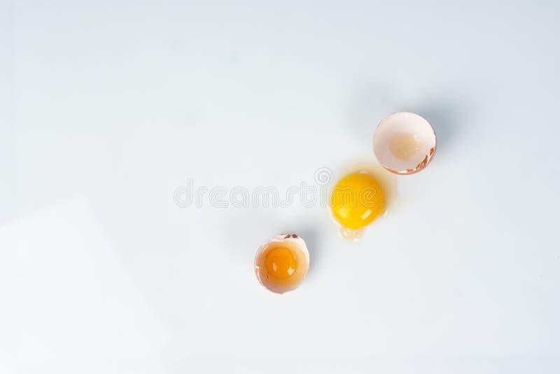 Gema de ovo quebrado na casca de ovo decorada com o ninho cor-de-rosa do sisal sobre fotos de stock royalty free