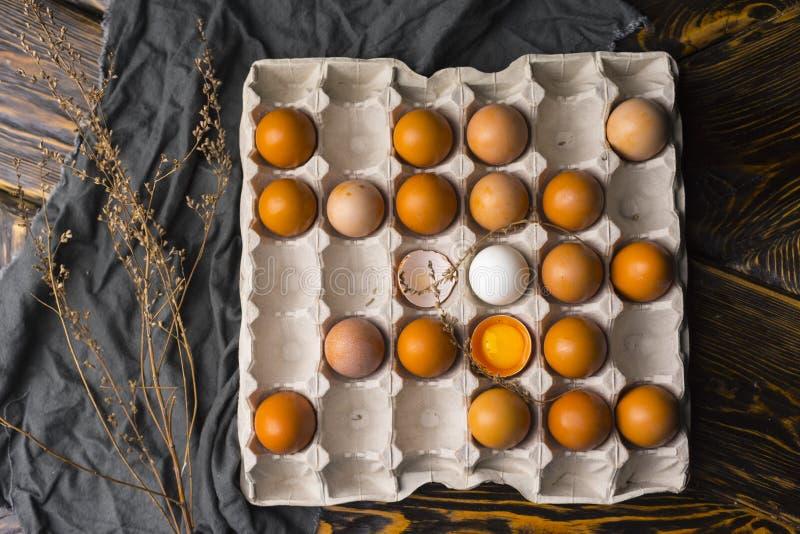 A gema de ovo quebrado na casca de ovo e diversos ovos na caixa egg a BO imagens de stock
