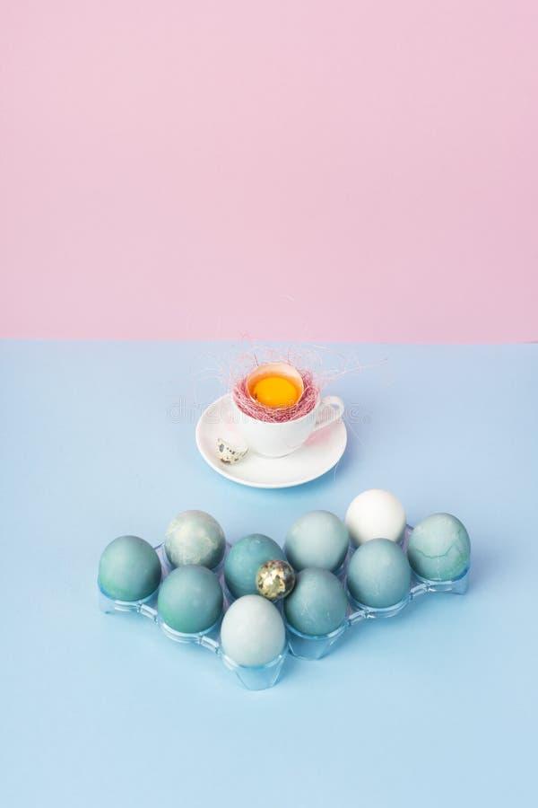 Gema de ovo quebrado na casca de ovo no copo de café branco em uns pires d fotografia de stock