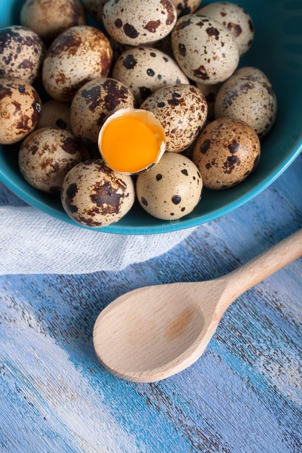 Gema de ovos das codorniz na colher e na gaze de madeira da bacia foto de stock