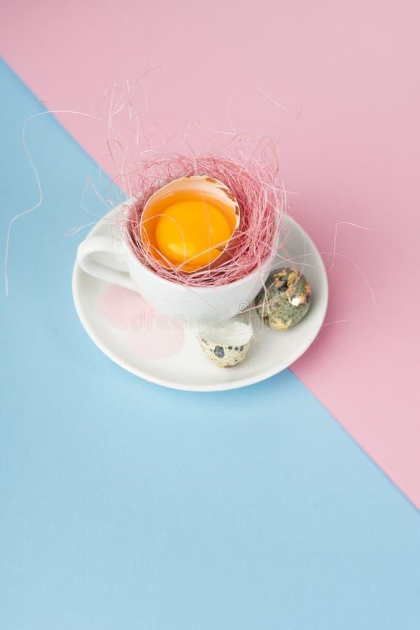 Gema de ovos quebrados no shell em um copo de café branco na imagem de stock royalty free
