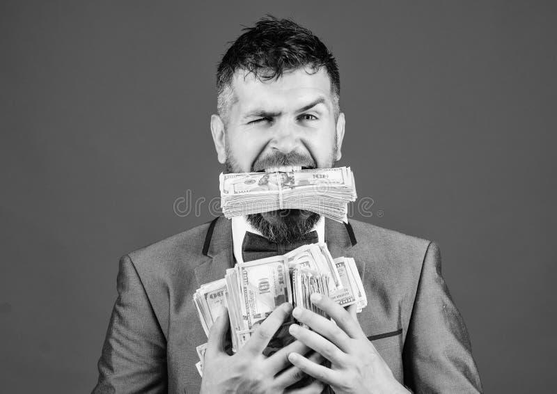 Gemakkelijke contant geldlening Houdt het mensen formele kostuum velen de blauwe achtergrond van dollarbankbiljetten Zakenman gew royalty-vrije stock foto
