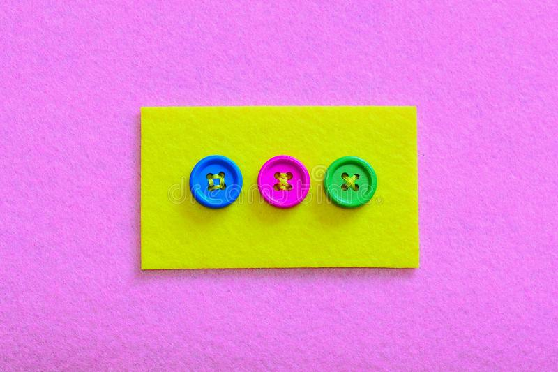 Gemakkelijke manieren om knopen aan gevoeld te naaien Geel gevoeld stuk met kleurrijke die knopen op roze gevoelde achtergrond wo royalty-vrije stock foto's