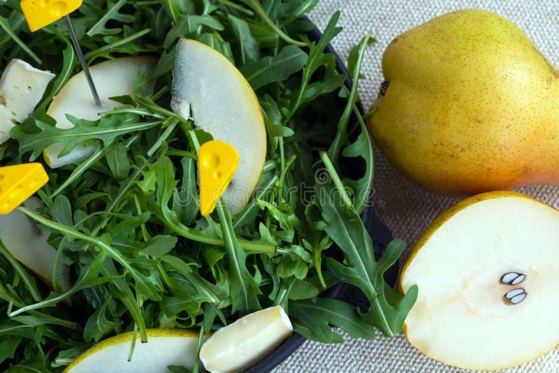 Gemakkelijke smakelijke de zomersalade met peer, arugula, Briekaas, pijnboomnoten, honingssaus E stock foto's
