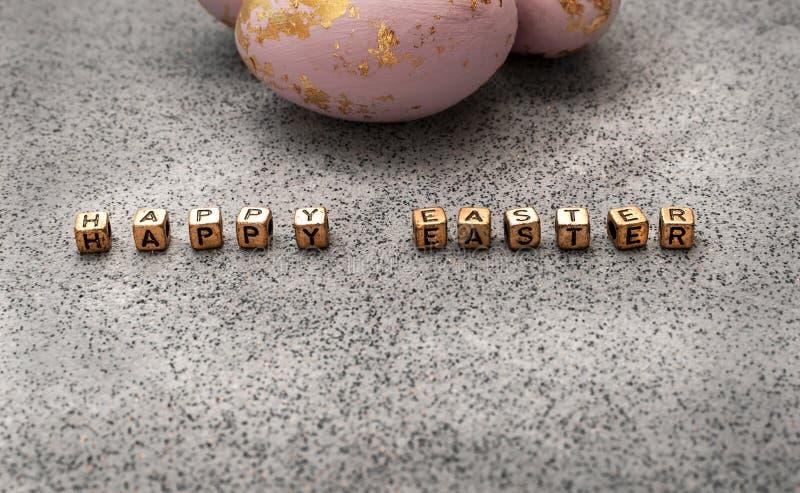 Gemalte Eier im rosafarbenen Gold und Buchstaben 'fröhlicher Ostern 'auf einem Schmutzbeschaffenheitsgranit oder einem konkreten  lizenzfreie stockfotografie