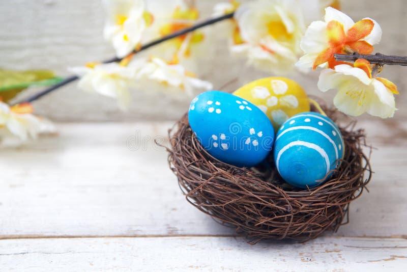 Gemalte Eier und Blumen Eier in den Nestern auf Holz stockbild