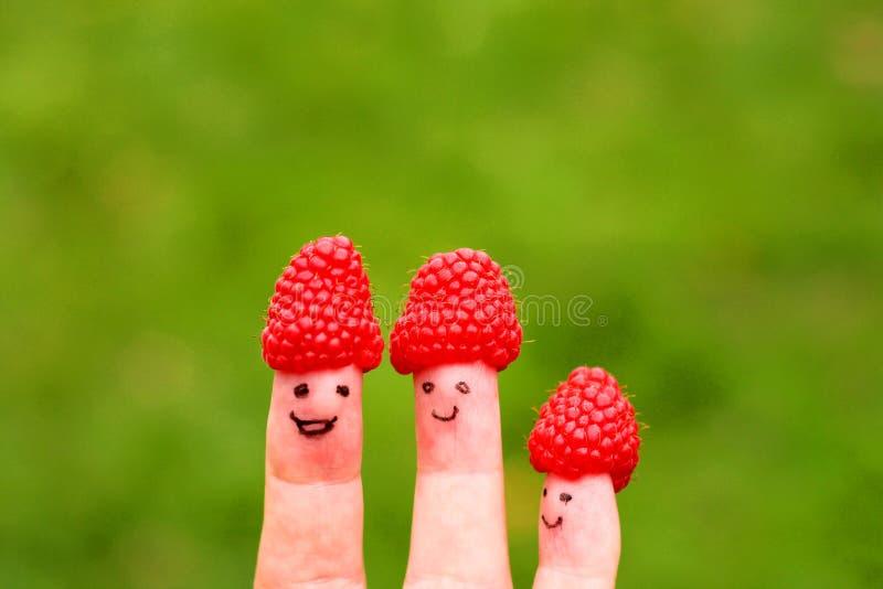 Gemalte Gesichter auf Fingern mit Himbeerhüten stockbilder