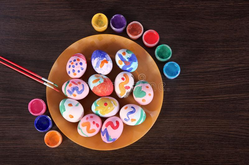Gemalte Ostereier, Malerpinsel und Farbe auf dem Tisch Vorbereitung für Ostern Hölzerne Tabelle stockbild