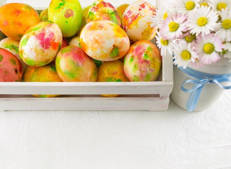 Gemalte Ostereier und Gänseblümchenblumen stockbild