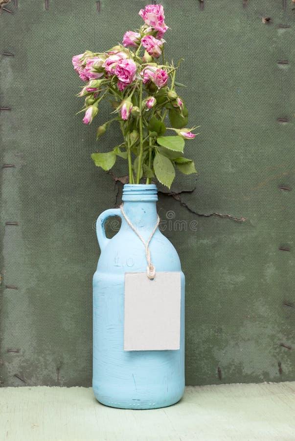 Gemalte Portugiesische Galeere mit Kraftpapier-Aufkleber Grüner hölzerner Hintergrund des Schmutzes Altes Flaschentagmodell Blaue stockbild