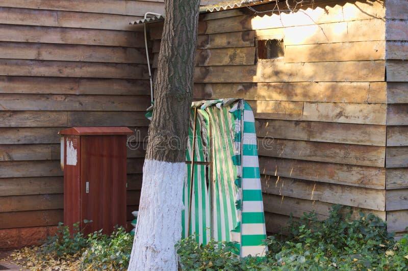 Gemalter Baum nahe einem Holzhaus, einem Behälter und einem gestreiften Vorhang stockbild