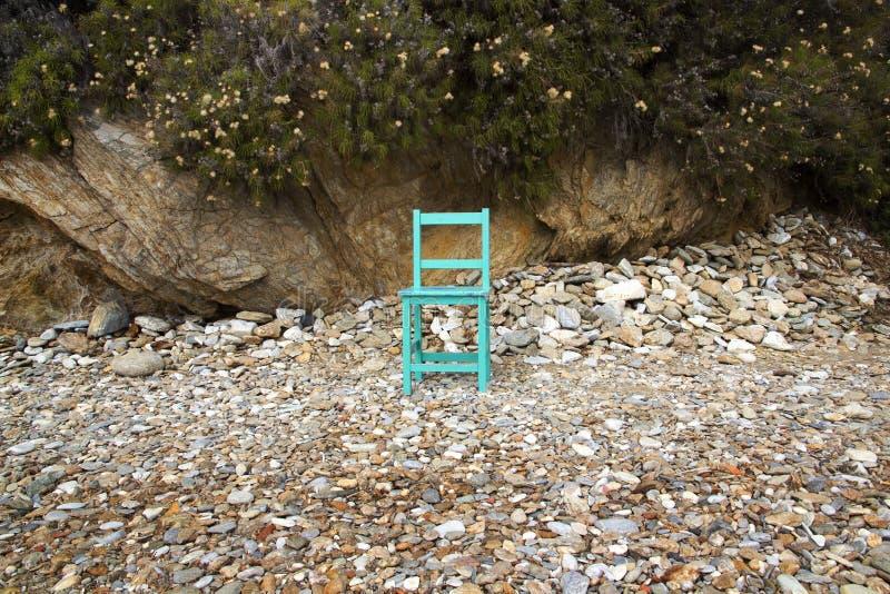 Gemalter Holzstuhl auf felsigem Strand stockbild