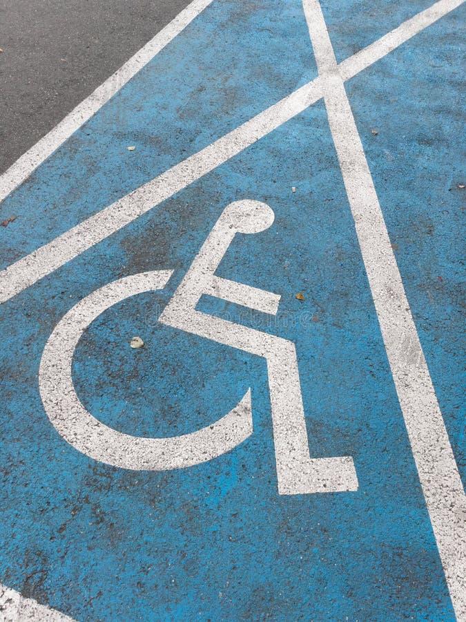 Gemalter markierender reservierter Parkplatz des Zeichens für behindertes und Behinderter stockbild