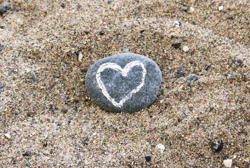 Gemaltes Inneres auf dem Stein, der im Sand liegt stockfotografie